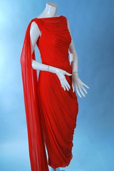 """Glamorous Ceil Chapman red silk chiffon classical goddess gown, dating to the 1950's. Masterful fluid draping of the silk chiffon to emphasize the curves of the female form, with cowl neckline, fan tail chiffon fluttering at the back. Lined in rayon crepe with stays thru the bodice, back metal zipper, long chiffon streamer off one shoulder. In excellent uncleaned as found vintage condition with one pindot ink spot lower front skirt. This has not been dry cleaned. Chest measures 36"""", waist…"""