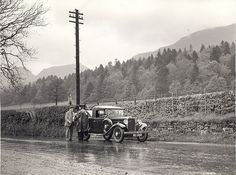 Sub Postmaster, Blanefield. A man stands beside a parked car on a road with its boot open. He is receiving parcels from a postman who is wearing waterproofs.