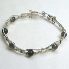 "Handmade gemstone labradorite bracelet features semi-precious round labradorite gemstones, sterling silver wire wrap, and hook clasp. 6 1/2"" in length. Add a necklace, pendant and earrings to complime"