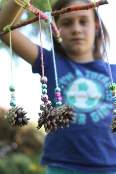 child-holding-homemade-pinecone-mobile