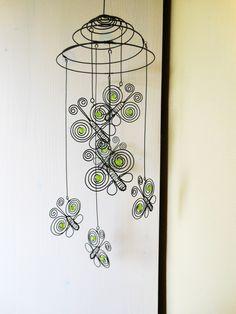 Motýlci na pružině - zelenkaví Závěs je vyrobený z černého žíhaného drátu a dozdobený korálky. Velikost motýlků je 6,5x6 cm. Délka celého závěsu je cca 42 cm. Průměr pružiny je caa 14 cm. Počet motýlků je 7 kusů. Závěs se nejlépe hodí do prostoru, na okno, lustr ... Drát je ošetřen proti korozi, ve velmi vlhkém prostředí může chytit patinu rzi. Možnost ...