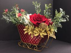 Christmas 2014 Season Faux Floral: Glitter mistletoe with Berry picks, frosted white hydrangea, red winter roses, mini golden poinsettias on tin red sledge vase. Original design & arrangement by http://nfmdesign.synthasite.com/