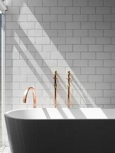 Un côté industriel chic  :  carrelage métro, robinetterie en cuivre mais une baignoire design un îlot | Industrial chic bathroom