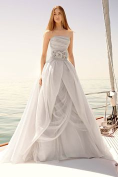 White by Vera Wang is a breathtaking designer wedding gown.  It features a beautifully cut bodice, a chic gemmed floral belt, and a beautifully draped skirt.
