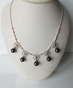 """Enjoy this beautiful white pearl """"Snowflake"""" necklace.  This #jewelry piece makes the perfect #holiday gift ! These delicate """"Snowflakes"""" Necklace features a sparkling white #diamond accent set above a lustrous freshwater #pearl. Pearl type: Freshwater Color: Black Brown, Pearl size: 8.5 mm, Shape: Round, Cultured pearls, Diamond weight: 0.46 carat (52 natural diamonds), Color: H, Clarity: I1, Setting: Prong, Metal: 14K white gold, Weight: 12.30 grams Length: 16"""" $660"""