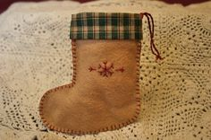 This stocking measures approximately 4 1/2 inches tall by 4 inches wide across the bottom. It is made of coffee colored felt and features an embroidered snowflake design in red, blanket stitch edging and homespun trim in green and cream. Perfect for holding a gift card, jewelry or other small gift. Can also be hung as a decoration.