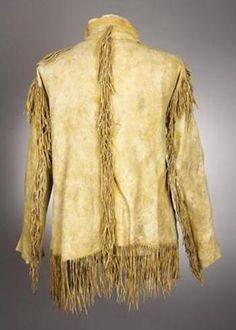A PLAINS PAINTED AND FRINGED HIDE SCOUT JACKETc. 1880 painted overall with yellow ochre paint and lined with red trade wool, trimmed with metal cones inserted with red-dyed horsehair, brass military buttons, and hide fringe Length: 29 inches excluding fringe Condition Report: Overall very good condition with usual wear and soiling. Hide with some stains. Hide fringe intact. Approx. 1 button missing. Fabric lining with insect loss.