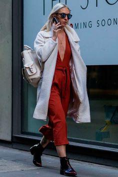 Street style look com macacão vermelho decotado e botas.