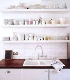 white floating shelves, white subway tile, white cabinets, wood counter