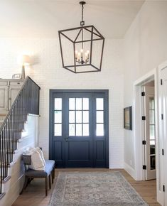 Foyer with dark paint front door, painted white brick wall, chandelier, white walls, transitional country farmhouse style. Style At Home, Porta Colonial, Sweet Home, Interior And Exterior, Interior Design, Interior Door, Affordable Rugs, House Goals, Home Fashion