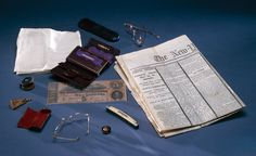 The contents of Abraham Lincoln pockets when he was shot at Ford's Theatre in Washington, D.C., included: a. linen hankerchief; b. eyeglass case; c. folding glasses; d. wallet; e. knife; f. cufflink; g. folding glasses; h. folding glasses case; i. watch fob; j. eyeglass cleaner/buffer; k. Confederate bill. The newspaper from the following morning reports the assassination.