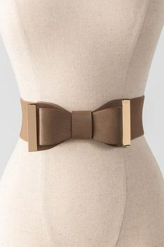 "Dress up your look with a bow!  This adorable taupe belt features a bow that sits front & center with gold hardware. <br><br>    -	28"" length x 2.5"" width<br>  -	Measured from small/medium<br>  -	Imported<br>"