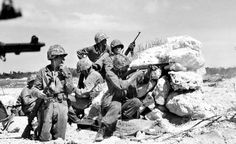 U.S. Marines of the 1st Marine Division cover behind rocks during a fight against Japanese on Peleliu, 1944.