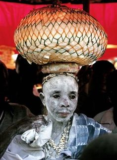 Africa | An Ashanti priest in Ghana who is covered with white kaolin and carrying a bowl of therapeutic potions on her head | Just one of the many fantastic photographs included in the publication 'Painted Bodies: African Body Painting, Tattoos and Scarification'