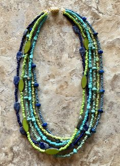 Two 3 strand beaded necklaces in blue, green, and turquoise seed beads, with green Picasso glass, blue lapis and magnesite bead accents. One necklace is Picasso seed beads and the other is solid seed beads. Wear separately or together for a fuller look.