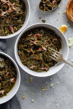 Overhead of three white bowls filled with Southern Collard Greens with hamhock against gray background recipe soul food meals Easy Collard Greens Recipe, Southern Collard Greens, Feta Dip, Food Network, Bbq, Southern Recipes, Southern Food, Southern Dishes, Baked Chicken