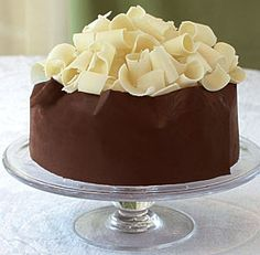 The simplest way to decorate this cake is to press chopped, toasted walnuts onto the sides. For a more dramatic look, try wrapping the cake in a chocolate band and topping it with white chocolate curls.