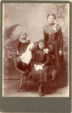 Cabinet card of 3 girls & a doll. Hand written on back is Kukelman girls.