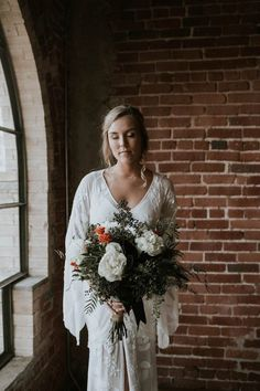 This bride opted for mostly greenery with white and orange peonies for a pop of color. With her floral embroidered flutter sleeve wedding gown and brick backdrop for her wedding photos, were getting major fall rustic wedding vibes. Here are some other peony wedding bouquets. // Photo: Janice Morgan