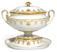 A porcelain tureen, Imperial Porcelain Manufactory, St Petersburg, Period of Nicholas I (1825-1855) - the white ground with gilt palmette borders centring Imperial eagles with ribbons and badges of the orders of Saint Vladimir and Saint George and inscription in Russian 'For Service and Courage', parcel-gilt scroll handles, the lid with rosette finial, on a spreading base, with blue Imperial cypher of Nicholas I height 31.5cm, 12 3/8 in.