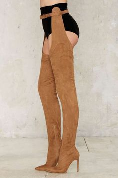 Let your boots do all the legwork—literally. The Maven Boot comes in soft taupe vegan suede, with a pointed toe, stiletto heel, thigh-high silhouette, extended sides, and connected belt at waist. Thigh and bye. By Jeffrey Campbell.