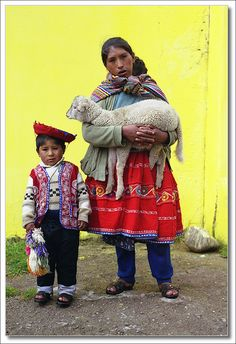 Peru, woman and child with lamb (or kid)