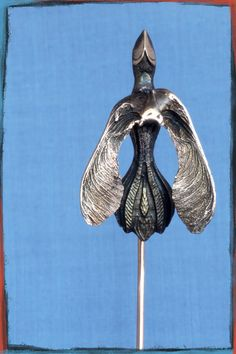 Take Wing pin in silver and bronze.