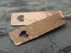 "Hammered Heart Earrings Valentine's Day Long by ATwistOfWhimsy, $32.00  Fun, rustic heart earrings. After cutting these rectangles from 22 gauge copper sheet, I used my jeweler's saw to cut the tiny heart shapes within. For a rustic effect, I hammered the rectangles and gave them a dark patina. They hang from sterling silver ear wires.   Length: 2-5/8"" (6.9cm) from curve of earwire Rectangles measure 1-3/4"" long x 1/2"" wide (44.5mm x 12.7mm)"