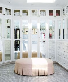 Stacks of drawers and seemingly acres of  mirror-door cabinets create a dressing room that's primed for grooming. With  its pleated skirt, a pink linen-upholstered bench offers a cushy, feminine spot  for lounging, trying on shoes, or perhaps even grabbing towels from upper  cabinets. The floor features polished marble tiles in a basket-weave pattern.