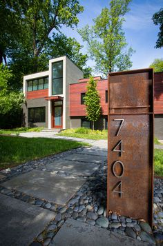 Weathered steel for custom mailboxes serving modern homes. This post, which also doubles as a mount for the address.