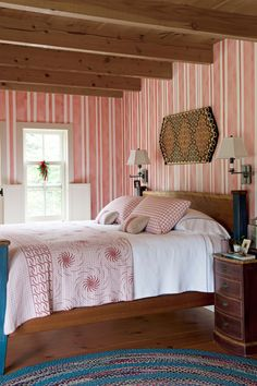 Love the pattern mixing in this bedroom with those exposed beams, rustic yet modern mix of striped wallpaper and quilts, etc.