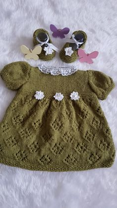 Stunning hand knitted baby dress set   READY FOR DELIVERY   This outfit is hand knitted by me, using baby yarn, soft and hypoallergenic, in a beautiful shade of olive green.  The set has a leaf lace pattern all around the skirt, 3 white satin flowers on the chest line, princess style short sleeves and organza collar. It also has 3 little white buttons on the back.
