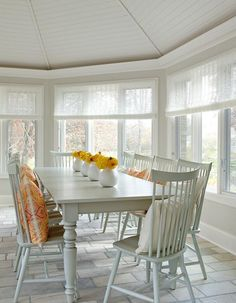 Yellow And Gray Sunroom Boasts A Vaulted Ceiling Over Farmhouse Dining Table Lined With