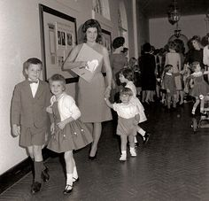 Jackie holds the hand of John, Jr. as the children arrive for Caroline's 5th birthday party in 1962.