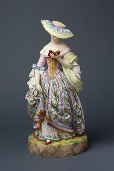 A Woman  Object: Figure  Place of origin: Paris, France (made)  Date: ca. 1862 (made)  Artist/Maker: Gille Jeune porcelain factory (manufacturer)  Materials and Techniques: Biscuit porcelain, painted in unfired colours and gilt