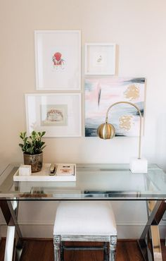 Chic home office space with a glass desk, a gold desk lamp, and a small gallery wall