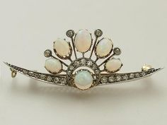 A diamond and opal aigrette/brooch combination, minus feather. Featuring five oval opals in a semi-circle, with diamond pinnacle spacers, rising from a base of an oval opal on a diamond base topped with a diamond crescent.