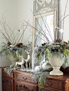 Layered urns (I would ask a florist for help!) with deer, ornaments, greenery and an over sized pine cone make this display one that will be remembered!