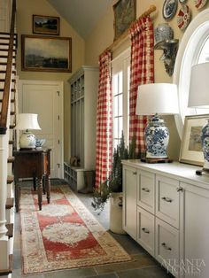 Farmhouse mud room. Classic blue and white relics ecco other traditional decors like an Oushak rug, mahogany buffet and red and white check curtains.  And the open storage area features hunting gear belonging to the designer's family and friends.