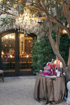 Outdoor table with chandelier hanging from a tree, glass french doors.