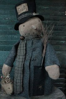 Frosty is 19 inches tall including his hat. He has been nicely aged with a hand-stitched face and a real dried carrot as a nose. He is weighted to stand on his own. He has an aged charcoal grey coat that he keeps closed with rusted wire and a couple of buttons. The tab on his hat has been hand-stitched and he has a small bird nest made of flax.
