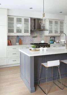 Seeded glass front kitchen cabinets flank a stainless steel vent hood mounted to gray and blue mosaic backsplash tiles above a polished nickel swing arm pot filler fixed over a stainless steel range.