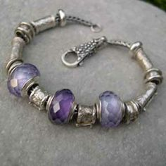 Wisteria Bracelet: dark purple CZ bead and silver bead detail; pale lilac CZ bead with silver core, & our textured silver beads. All the beads are interchangeable, and slide on and off the silver bracelet chain, with a detachable silver clasp to secure them. Collect more beads over time, to design your own bracelet.