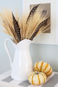 Pheasant Feather Floral Arrangement — this simple yet stylish arrangement by Summer from Simple Stylings adds stalks of wheat to the pheasant feathers and arranges them in a white pitcher.