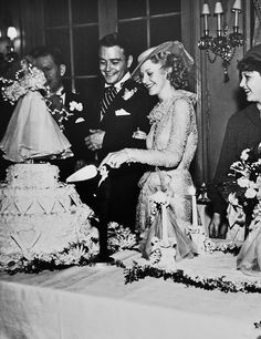 Ginger Rogers and Lew Ayres cutting their cake on their wedding day