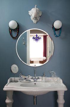 Vintage, diseño y audacia. Lavabo blanco con patas, espejo redondo y busto de elefante en la pared