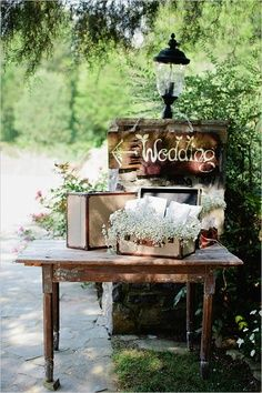 Cute! Maybe some Spanish moss a few flowers for color in place of baby's breath. Like the hand painted sign too (Gift table?)