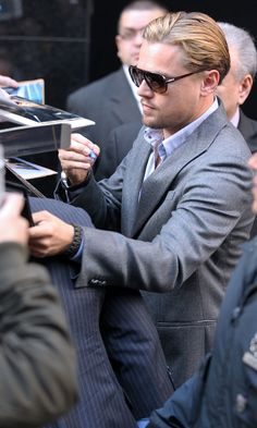 His hair is looking a bit blonder here as he signs autographs for his adoring fans. | Leonardo Dicaprio