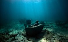 Inertia - Underwater Sculpture by Jason deCaires Taylor - Underwater Museum in Cancun, MX - an overweight man sitting in front of TV surrounded by rubbish thrown carelessly around him; an amazingly detailed sculpture down to the remote control, sofa cushions, and hamburger and fries on his lap. This figure is pretty self-explanatory as well and continues to show mankind's carelessness and how we pollute our planet. TV has holes so that sea life can enter and is a great breeding ground for…
