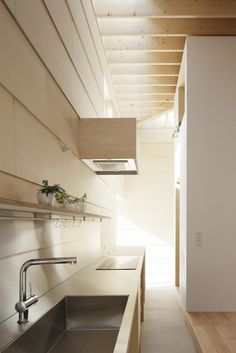 """stainless steel sink... The architects suggest that the spaces between the elevated rooms be considered as roads through the """"town"""" that is the home."""